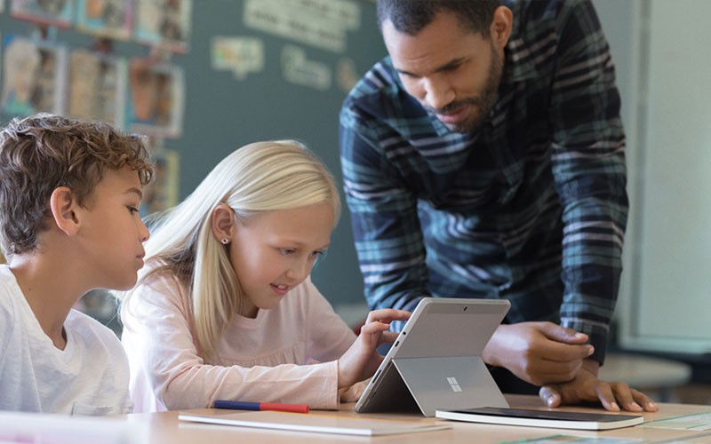 Teacher uses Surface device to teach two students in classroom